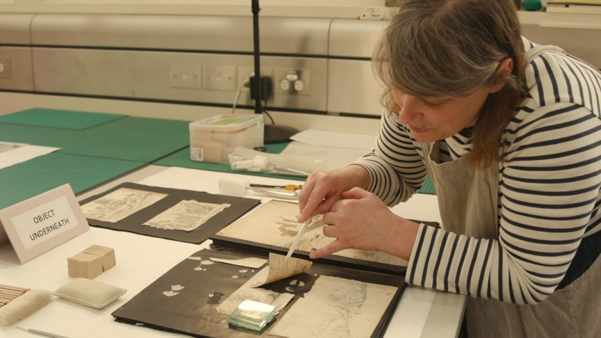 A woman with a scalpel gently prods some historic documents