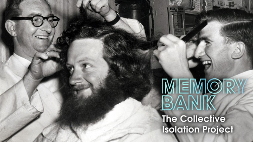 A man with a big beard and hair receives a trim while three other men look on smiling