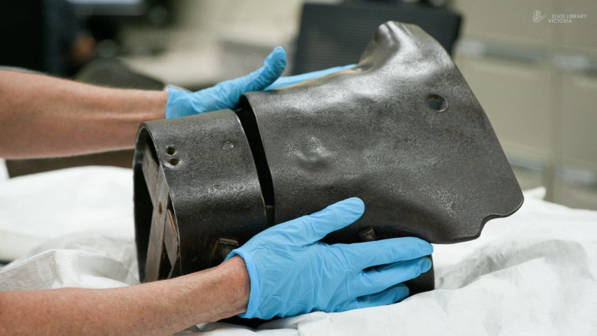 Two hands with blue gloves on holding a metal helmet