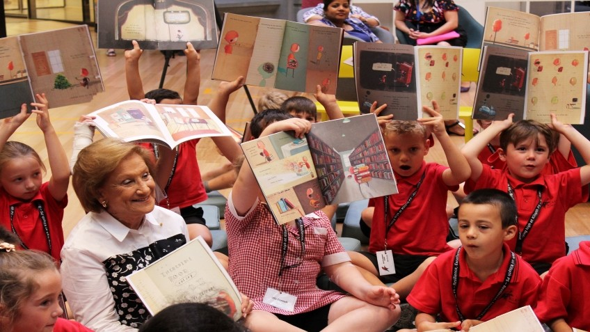 Children in red uniforms hold up books while an older woman smiles at them