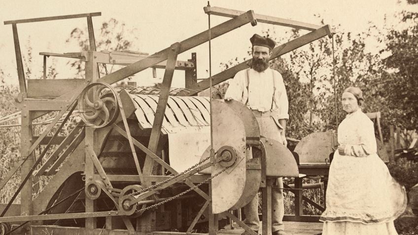 A 19th century man and woman stand behind a large piece of farm equipment