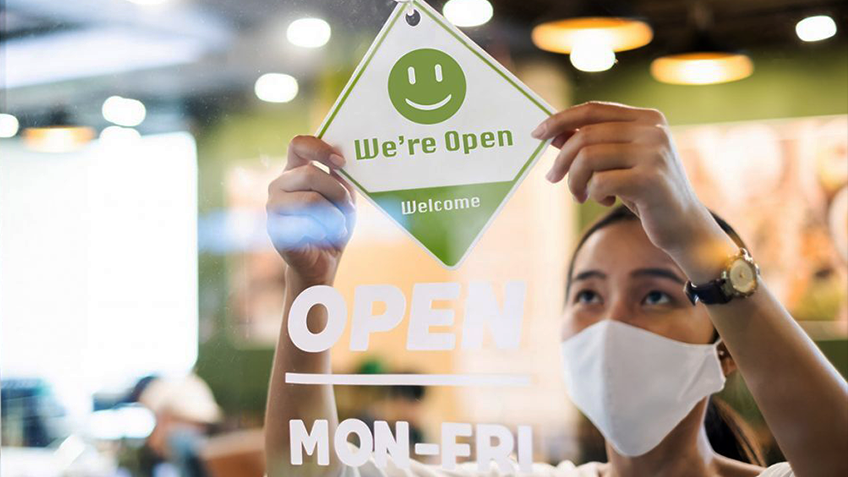 A woman wearing a face mask places a 'Welcome' sign on a shop door