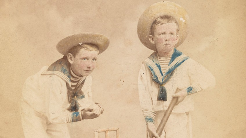Sepia postcard of two cherubic boys in sailor outfits playing cricket