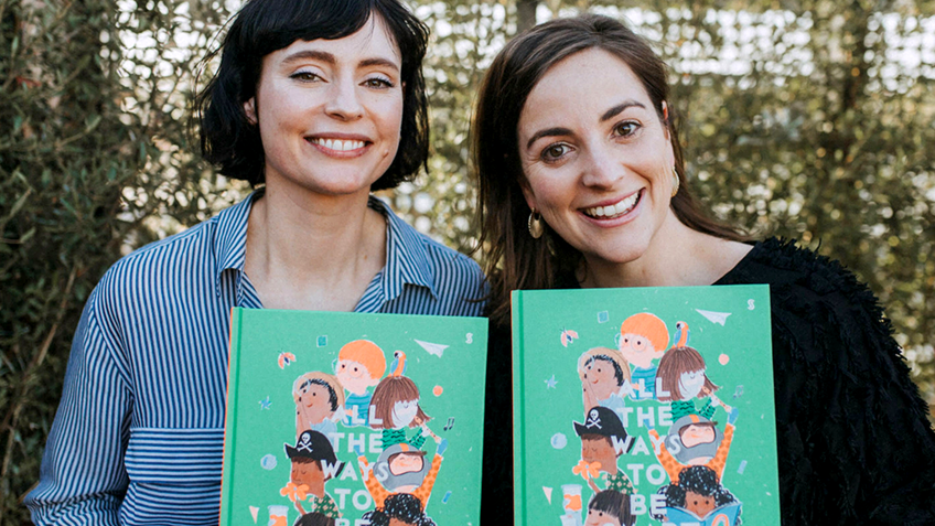 Two smiling women hold up picture books