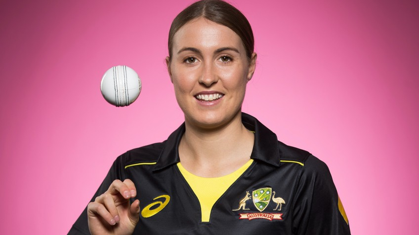 A woman spins a cricket ball against a pink backdrop