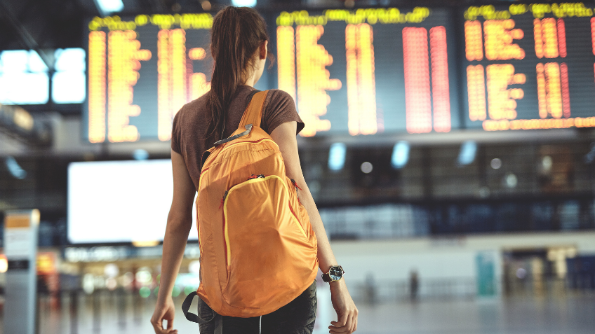 Woman standing in front of an airport arrivals board