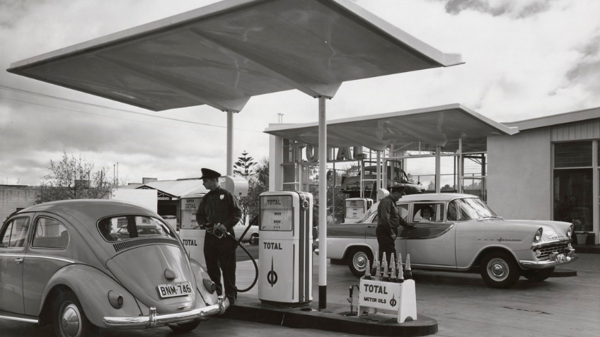 Black and white photo of two men filling the petrol of two cars