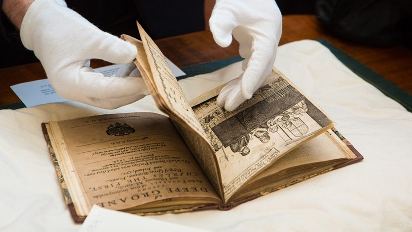 A pair of gloved hands turn the pages of a rare and valuable book