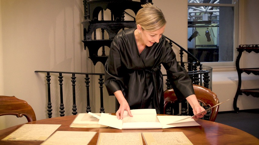 A woman leafs through piles of paper on a table