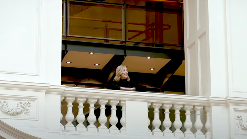 A woman in a black outfit stands on an ornate, white balcony indoors