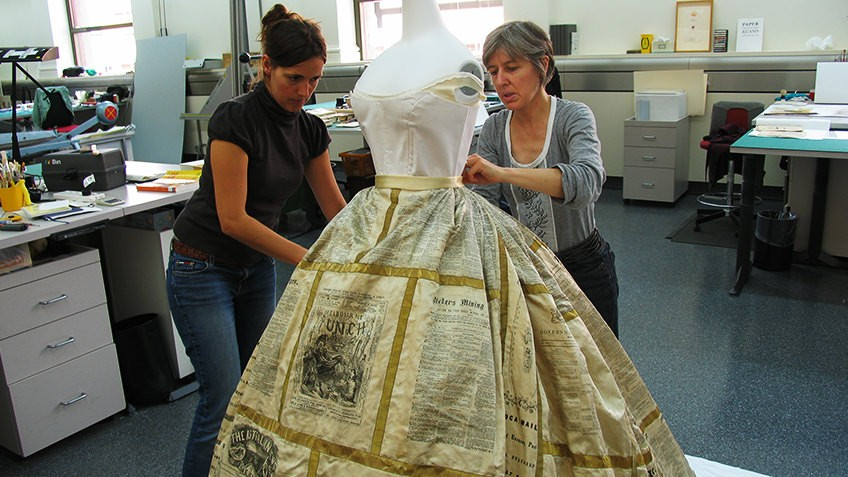 Photo of two women putting the Press Dress on a mannequin