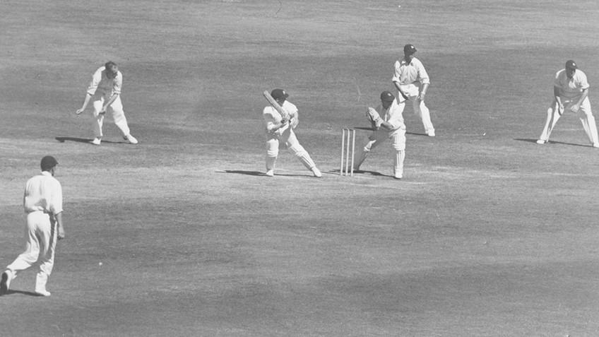 Men in white playing cricket