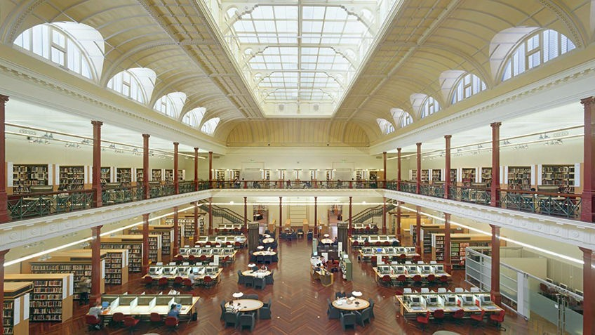 two-storey gallery with ornate glass roof, library stacks, desks and chairs