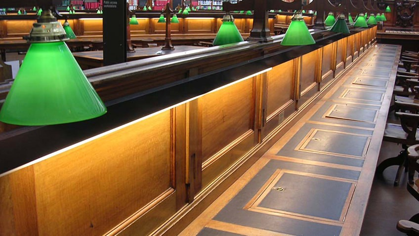 Photo of wooden desks and green lamps in the La Trobe reading room