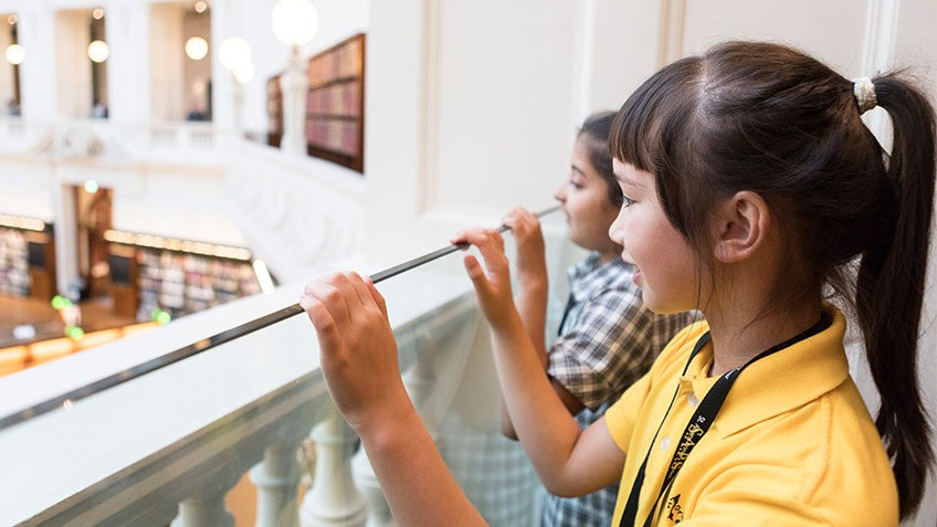 schoolgirls peering over the ornate balcony of a Dome Gallery in the octagonal La Trobe Reading Room