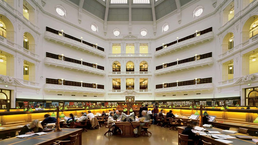 People sitting at desks in the La Trobe reading room