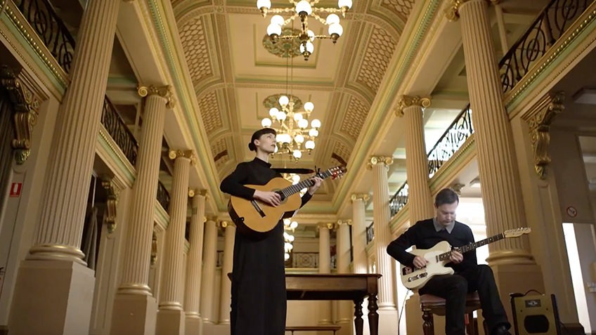A woman and man play guitar in a grand, two-storeyed Victorian room