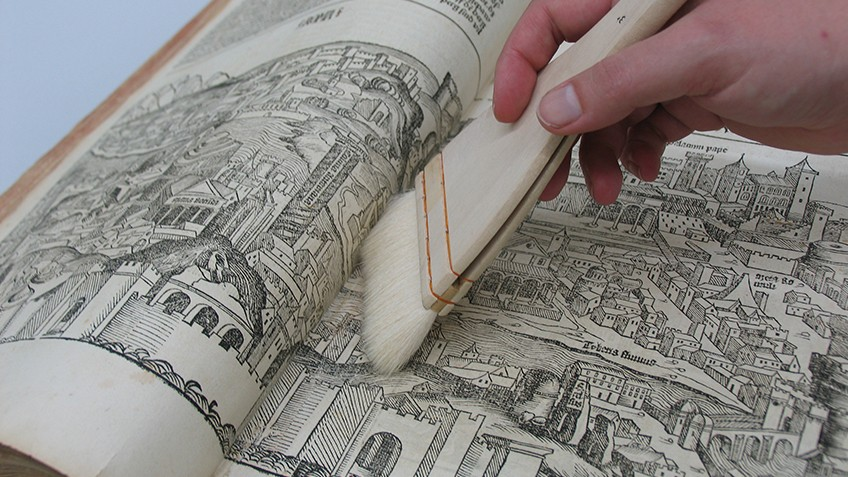 Colour photo of Library conservation team using a soft brush on an antique book