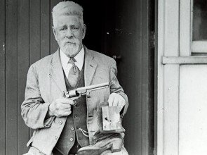 Man with beard holding pistol and boot