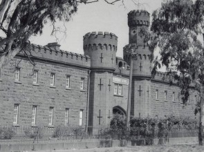 B&W photo of forbidding bluestone building with windows, watchtowers and turrets