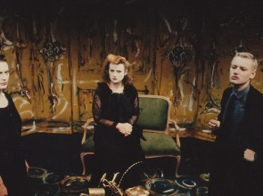 Two women and a man all wearing black stand on a stage set painted to look like a house interior