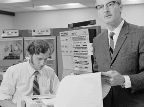 B&W photo of two men in 1970s attire standing next to an IBM computer, a dot matrix printer and reel-to-reel machines