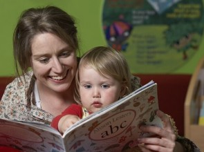 Photograph of mother reading a story to child