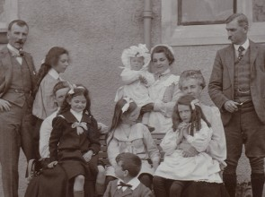 Black and white photograph of a family in front of house, c 1900