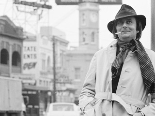 Black and white photograph of Barry Humphries standing on street
