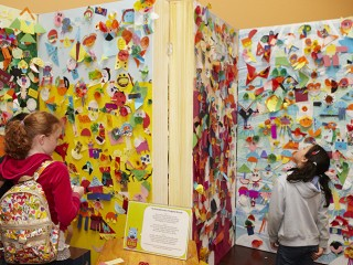 Photograph of children looking at a wall of collage and craft