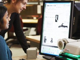 Colour photo of person using a computer and being helped by staff at State Library Victoria