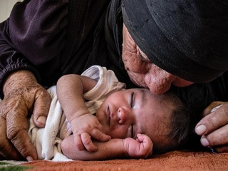 Photograph of woman kissing baby in Syria