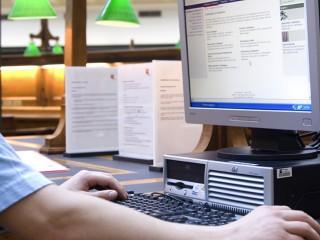 Colour photo of a person using a computer in the La Trobe Reading Room, State Library Victoria
