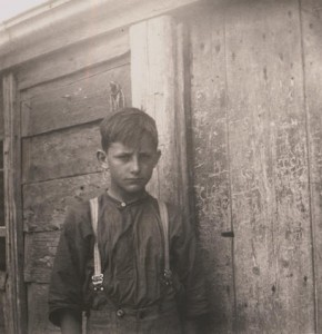 Photo of a boy standing in front of the back door of the Kelly Homestead