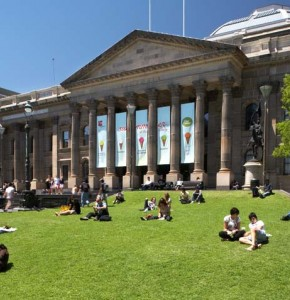 Colour photo of the State Library Victoria facade and lawn with people relaxing by Andrew Lloyd
