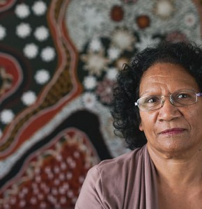Photo of Aboriginal woman standing in front of an Indigenous dot painting