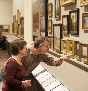 Photograph of visitors in a gallery looking at paintings