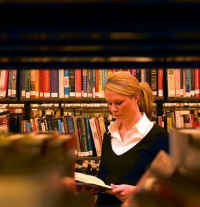 Library user in stacks surrounded by shelves of books