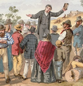 ST Gill colour watercolour showing a preacher speaking while his arms are spread wide, holding a bible in his left hand, with a group of people standing around him, with a coffee tent, mine shafts and huts in the background.