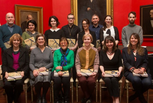 2015 Creative Fellows group shot against red walls and paintings of Red Rotunda