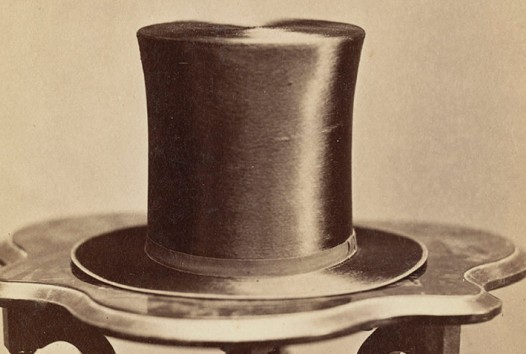 Sepia photograph of Victorian-era top hat sitting on a carved wooden table