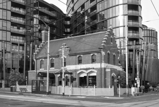 Black and white photo of a small building nestled amongst large buildings