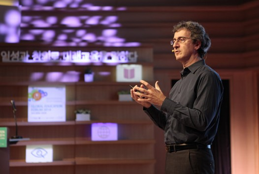 Photo of a man lecturing on a podium with a screen behind him