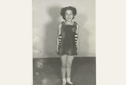 B&W photo of young smiling girl holding two striped batons