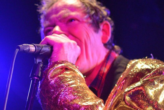 Photo of a man wearing a gold jacket singing into a microphone