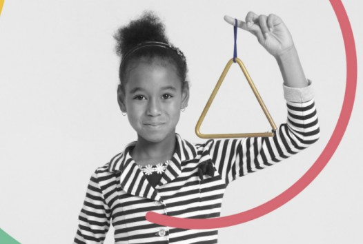 Child holding a triangle musical instrument