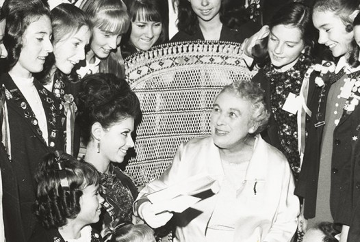 Young women surround a chair in which a beaming older woman sits as she is handed a book