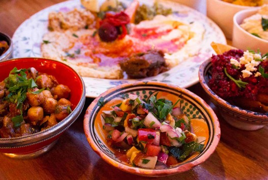 table with bowls and plates of Middle Eastern food including salads and dips