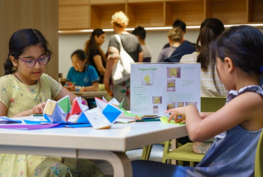 Young girls make paper origami at a table