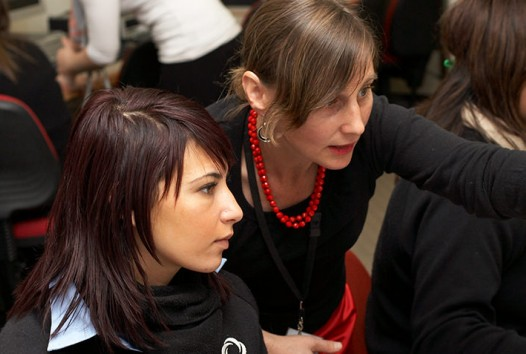 A teacher assists a female Year 12 student at a computer